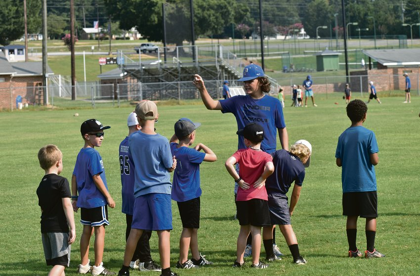 Peyton Smith instructs his team how to hit during the Little Rocks Baseball Camp last week at Person High School..