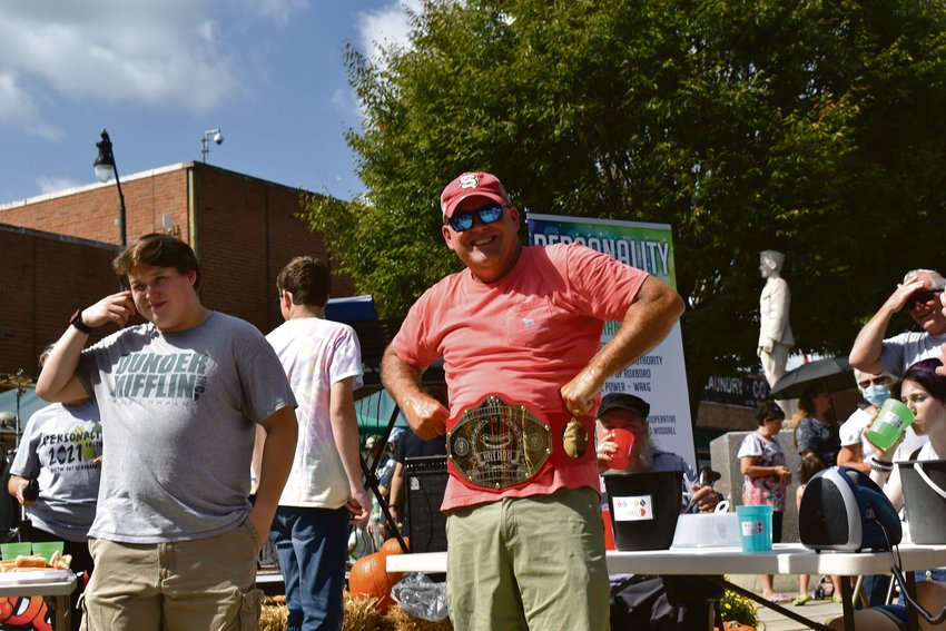 Former Person County commissioner Tracey Kendrick shows off his championship belt after defending his title of the hot dog eating champion during Saturday's Personality Festival.