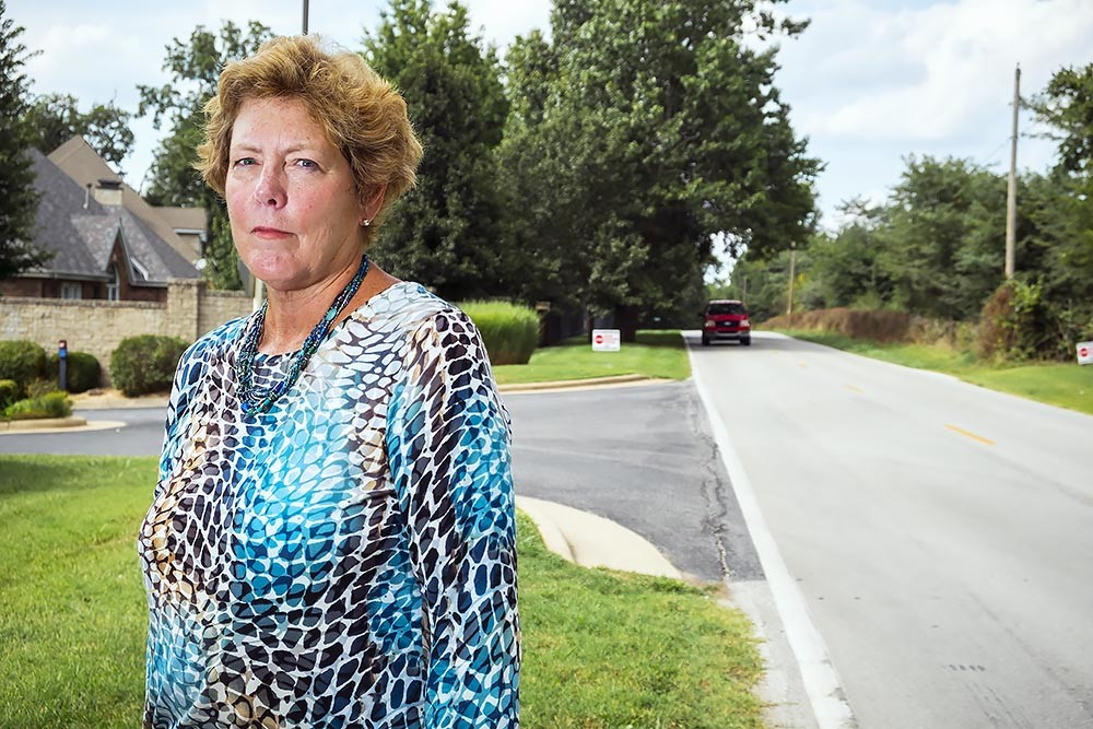 TAP THE BRAKES: Jane Paul stands on the shoulder of Kansas Avenue, a two-lane street the county plans to expand. Her North-South Corridor Alliance opposes the project.