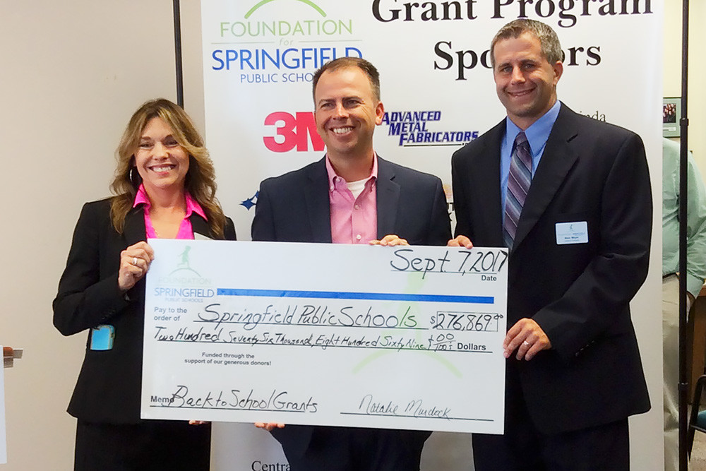 Foundation for Springfield Public Schools Director of Development Pamela Anderson, far left, and board President-elect Marc Mayer deliver a check to SPS Superintendent John Jungmann, middle.