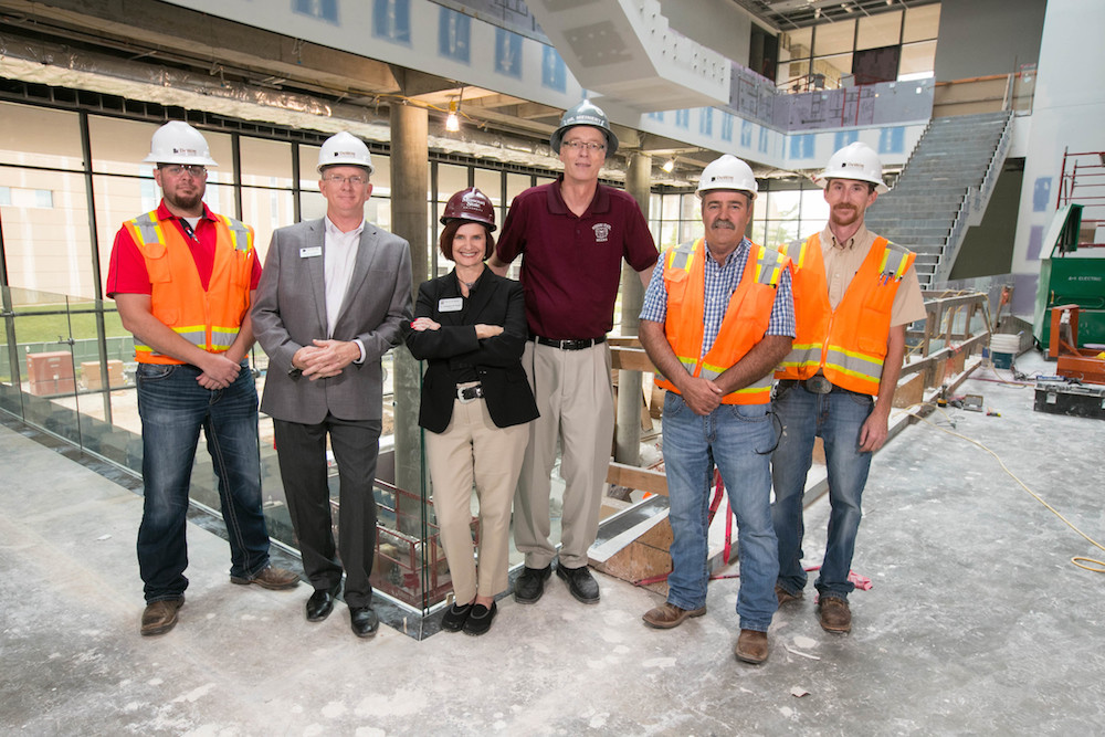 David Meinert, center, wearing maroon, stands inside Glass Hall with College of Business Dean Stephanie Bryant amid renovation work. Meinert is taking over in an interim capacity.