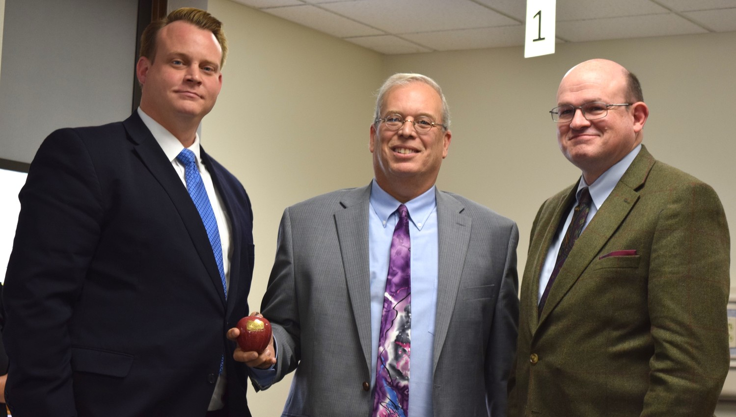 Skaggs Foundation grant committee member Matt Trokey, center, awards a ceremonial apple representing grant funding to Ozarks Technical Community College Table Rock Dean Robert Griffith, left, and Chancellor Hal Higdon.