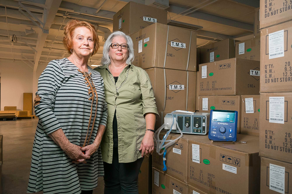 DETECTIVE TECHNOLOGIES: Paulett Anderson, left, and LeAnn McKee stand beside boxes of products. One, the MBI camera, boasts a 97 percent negative predictive value for detecting cancer.
