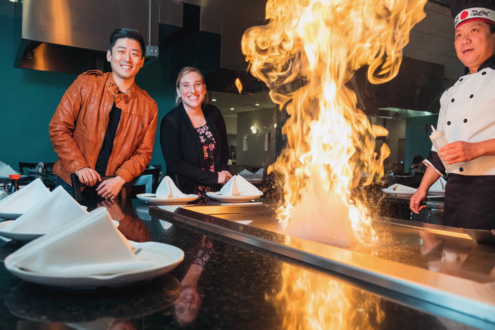 ASIAN FLARE: Co-owner Cosmo Kwon, HR Manager Megan Morano and Nixa head chef Jay Tan show off a teppanyaki grill at Hinode Japanese Steakhouse in Nixa.