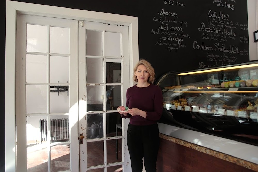 European Cafe co-owner Uliana Komodi stands in front of 100-year-old double French doors leading into the cafe's new space.