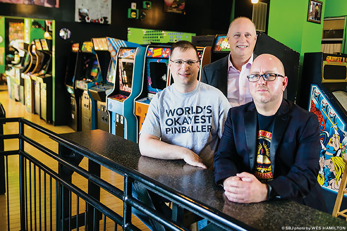 VINTAGE VIBES: 1984 owners Jason Durham, left, Devin Durham and Chris Stuart say arcade patrons can time travel toward the '80s.