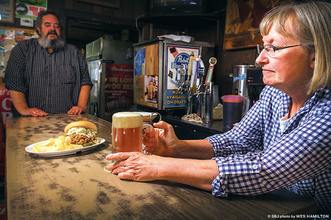 COMMUNITY CONNECTION: Pappy's waitress Debra Keese serves up a cold beer and a smoked pork sandwich. Her husband, Scott, co-owns the Grant Beach establishment.