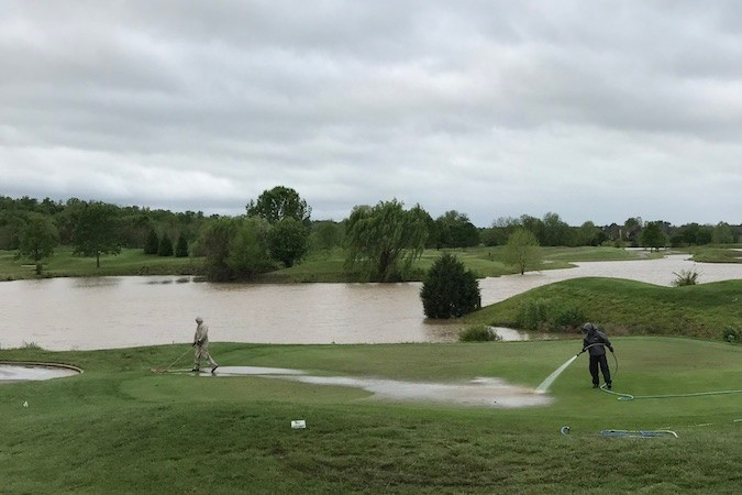Workers clean muddy river water off Rivercut Golf Course on May 1 after the James River covered its front nine holes. Greene County experienced close to 5 feet of rain the prior weekend causing Gov. Eric Greitens to declare a state of emergency.SBJ photo by ERIC OLSON