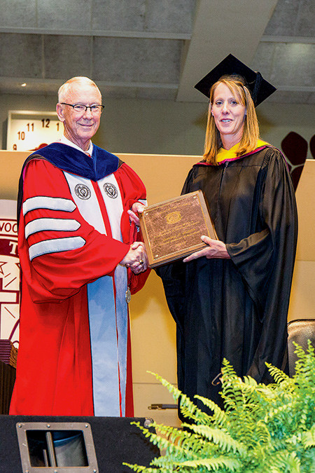 Tammy Holder, College of the Ozarks associate professor of agriculture, receives The Mildred Letton Wittick Professional Achievement Award from President Jerry Davis during the 110th graduation ceremony May 7. The award honors faculty members for work in research, publications, performances and creative productions.Photo provided by COLLEGE OF THE OZARKS