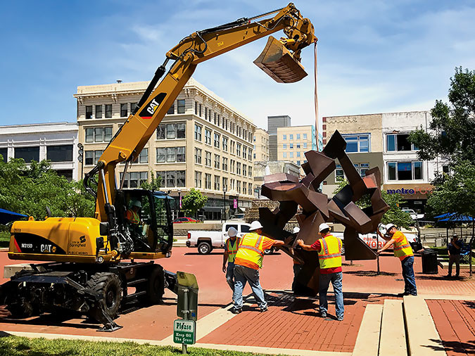 "Downtown Springfield's steel sculpture ""The Tumbler"" made a special tumble June 21 in honor of longtime supporter and former Coffee Ethic co-owner Tom Billionis, who died last year. Rotated at the start of each season, this tumble coincided with Billionis' birthday and included a plaque dedication for his support of downtown revitalization.SBJ photo by EMILY LETTERMAN"