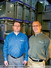 Custom Metalcraft International Sales Manager Greg Macchi, left, and TranStore Division General Manager Scott Higgins stand in a group of TranStore intermediate bulk containers. The Springfield manufacturing company sold $3 million in exports in 2011.