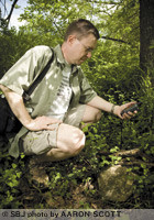 John Curtis, a Springfield optometrist, uses a hand-held GPS to locate a geocache hidden under rocks and sticks near the Wilson's Creek Greenway. He estimates that there are more than 400 geocaches hidden in a 20-mile radius from Missouri State University.