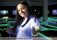 Lunar Mini Golf employee Crystal Brennan displays a phosphorescent golf ball used at the glow-in-the-dark miniature golf course in Battlefield Mall.