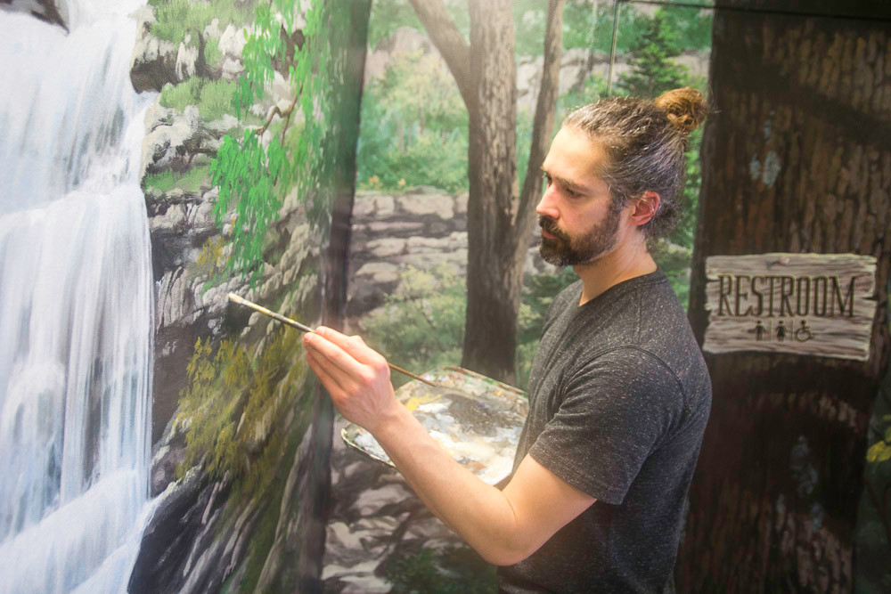 Artist Aaron Wolken finishes an outdoor-themed mural in the pool room.
