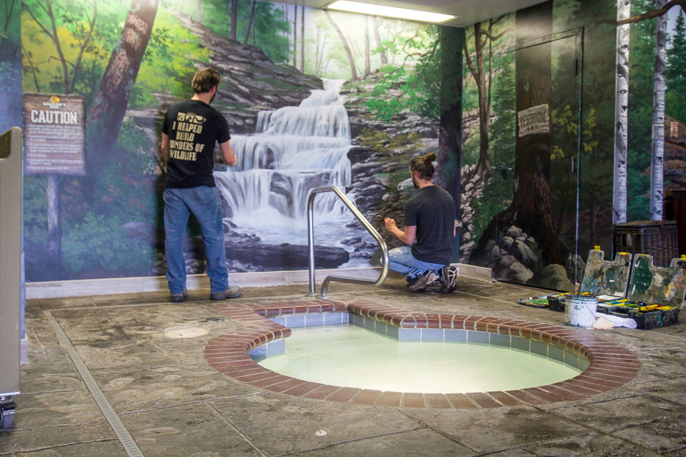 Brothers Adam, left, and Aaron Wolken paint a waterfall behind the hotel hot tub.