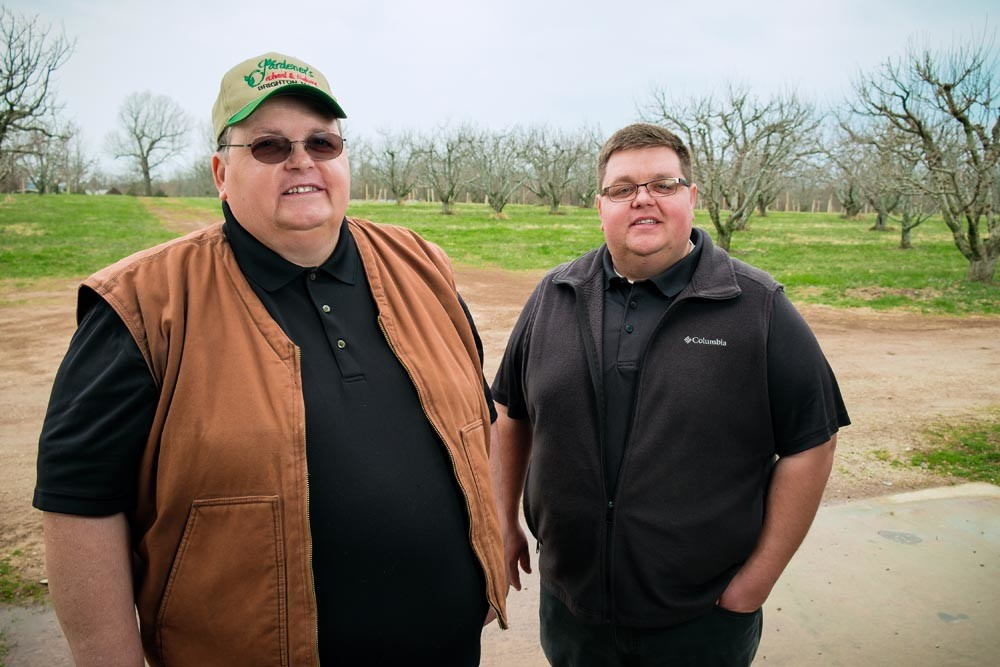 FAMILY FARM: Cornelius Gradinariu, left, fled Romania and ultimately settled at a Brighton orchard, where his son Radu, right, works as an account manager.