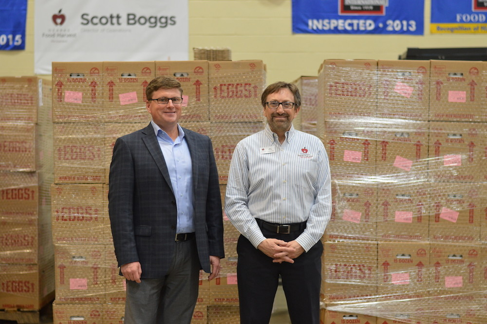 Opal Foods President Brock Peterson, left, visits Ozarks Food Harvest, represented by CEO Bart Brown, during the delivery of 280,800 eggs.