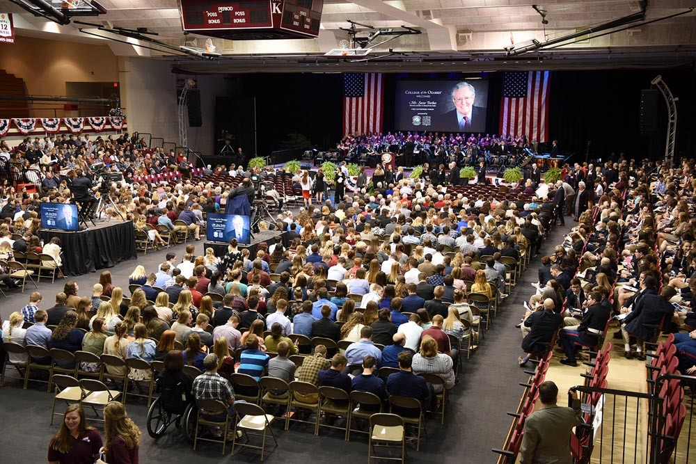 The campus gymnasium is full to hear Forbes. He spoke on federal tax and health care reforms, and promoted free-market economics.