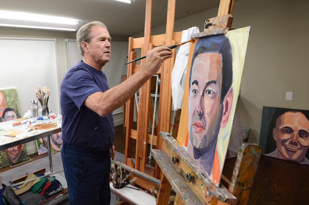 "George W. Bush paints one of the works in his ""Portraits of Courage"" art exhibit. The paintings are on display at Wonders of Wildlife through July 5."