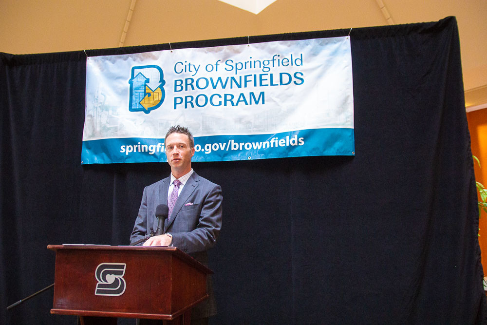 During Economic Development Week, officials discuss a $300,000 brownfields grant, and others celebrate $200,000 for green jobs training during a May 9 news conference. Above, Greene County commissioner Lincoln Hough credits three city-county partnerships representing 145 new jobs and $8 million in new capital.