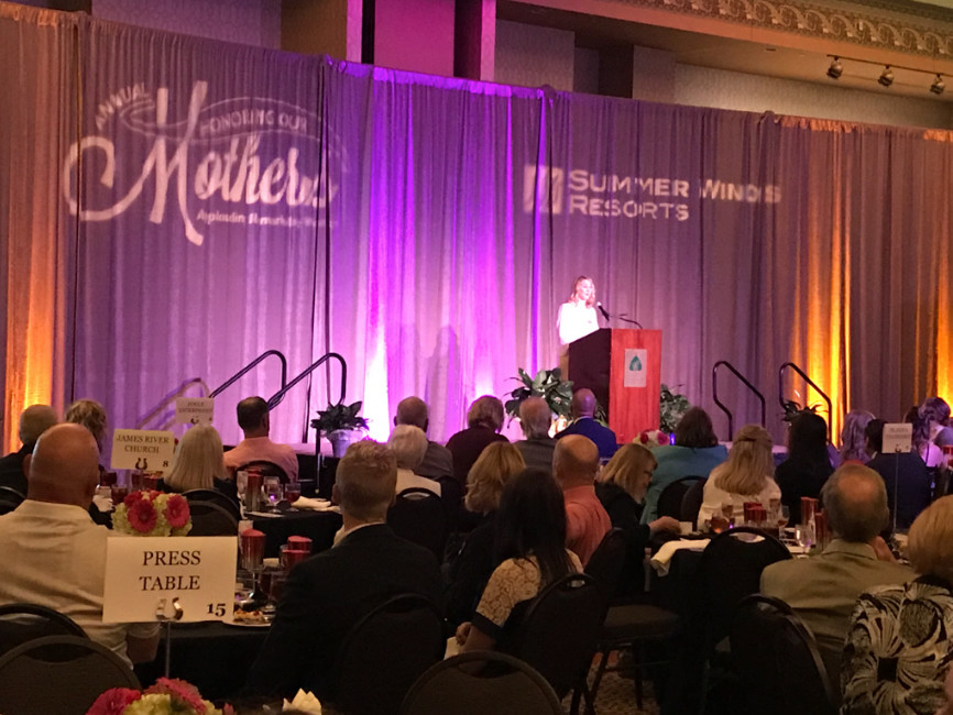 Anne Herschend McGregor welcomes the crowd to Chateau on the Lake  May 4 during The Caring People's banquet honoring single mothers. She spoke on behalf of her parents, Peter and JoDee Herschend, who were at Mayo Clinic for JoDee's cancer treatments.