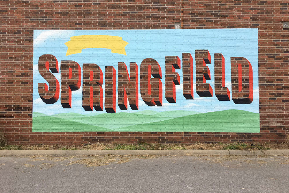 "Artist Andrea Ehrhardt is preparing a ""Greetings from Springfield"" mural on the brick wall of the Discovery Center."