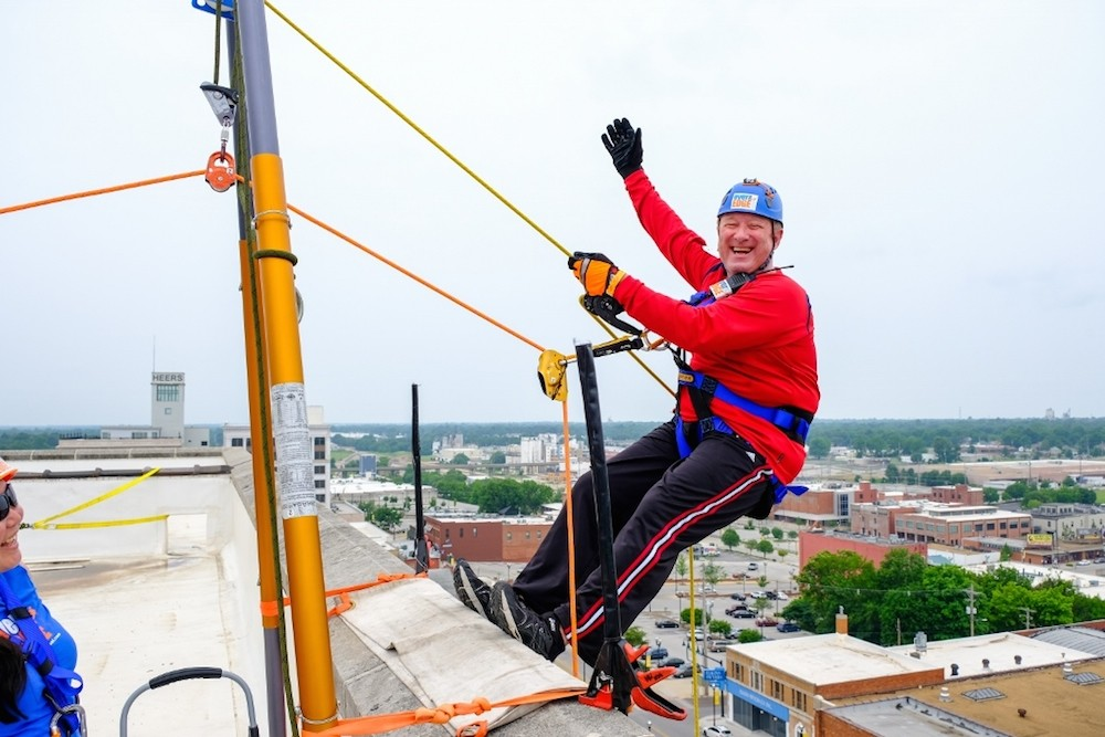 Jack Henry Banking President Stacey Zengel prepares to rappel down Sky Eleven to raise money for Child Advocacy Center. He personally raised $6,730.