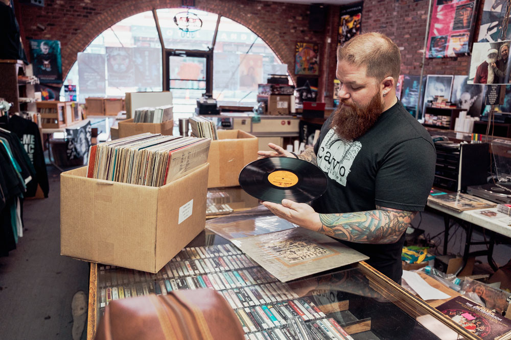 BUSINESS SUPPORT: Manager Erik Milan organizes albums at Stick It In Your Ear. Store owner Wes Nichols signed a pledge in support of increasing Missouri's minimum wage.