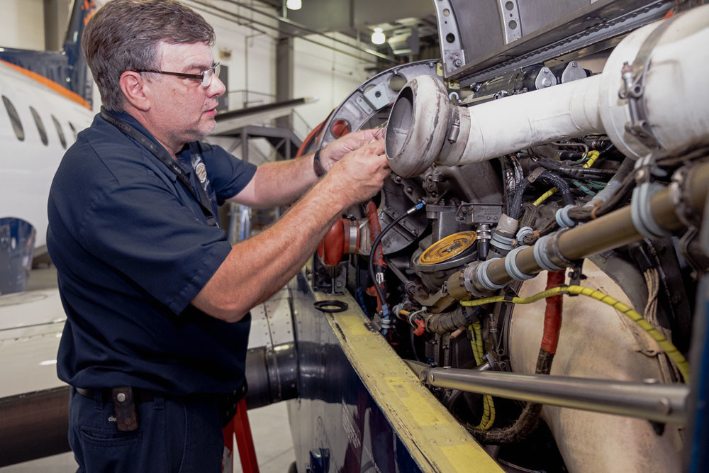 Dave Powell, shop manager, works on an engine in the hangar of Worldwide Aircraft Services.