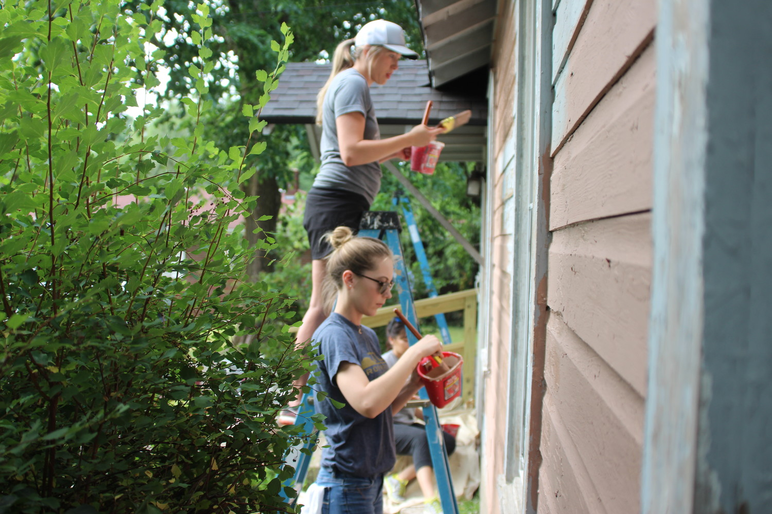 Volunteers paint a home in Woodland Heights during a June Rock the Block neighborhood cleanup event.