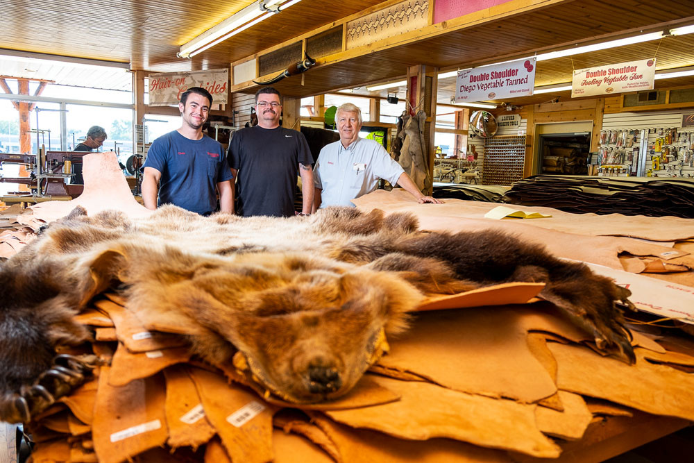 TOUGH CANVAS: Piles of leather several feet tall are a standard sight at Springfield Leather Co., run by Assistant Manager Chris Costa, far left, General Manager Rusty Darnell and owner Kevin Hopkins.