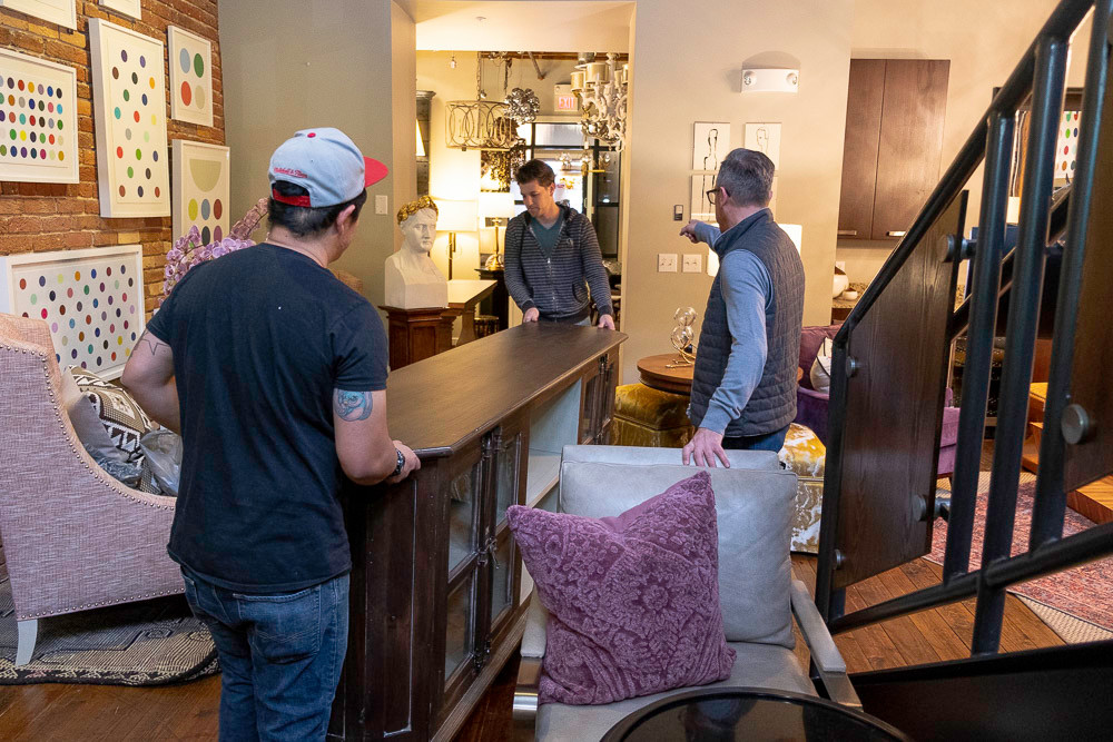 Obelisk Home co-owner Nathan Taylor directs employees as they move furniture onto the sales floor.