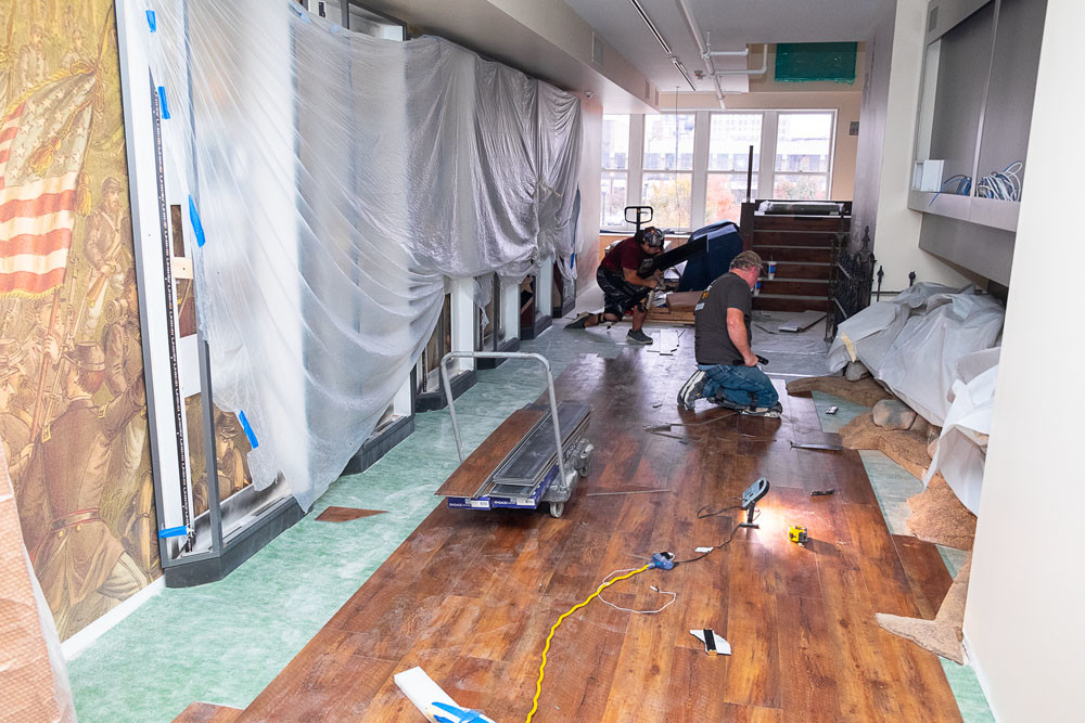 Workers install wood flooring in the second-floor Civil War exhibit. Some artwork already has been placed.