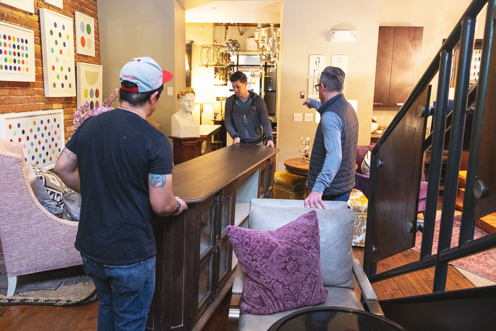 Obelisk Home co-owner Nathan Taylor, right, directs employees moving furniture onto the sales floor.