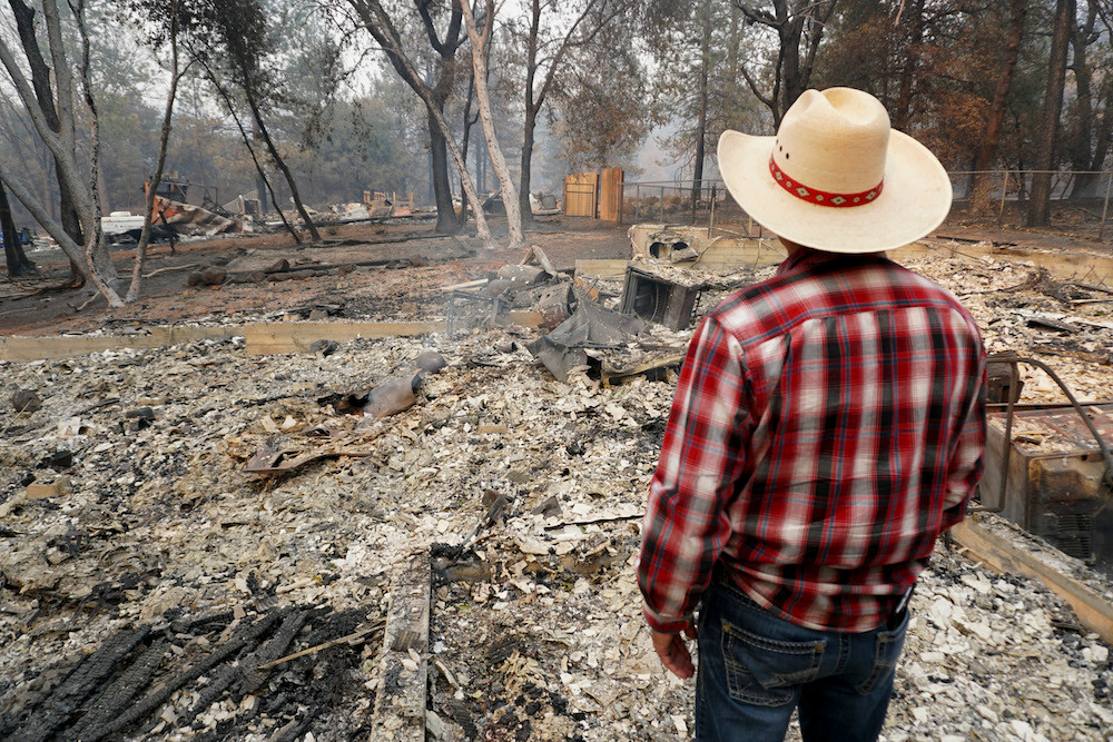 A man stands before ashes left behind by California's Camp Fire in a picture provided by Convoy of Hope. Pictured is the senior pastor of the First Assembly of God in Paradise, California, who lost his church and home in the fire.