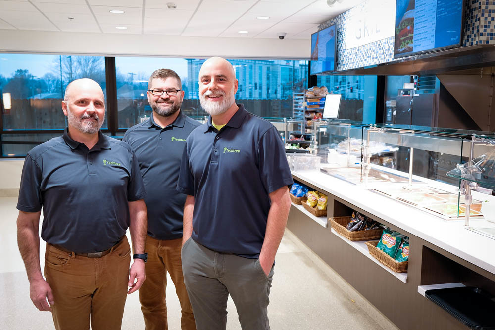 NETWORK ROOTS: J.J. Martin, Rick Manweiler and Jeff Dixon, left to right, of Techtree Partners stand in Mercy Hospital's new cafeteria. The firm spent 18 months installing the electronic menu boards, security cameras and other network systems.