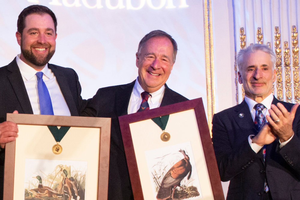 Johnny Morris, center, accepts the Audubon Medal with his son John Paul, left, and National Audubon Society CEO David Yarnold, right.