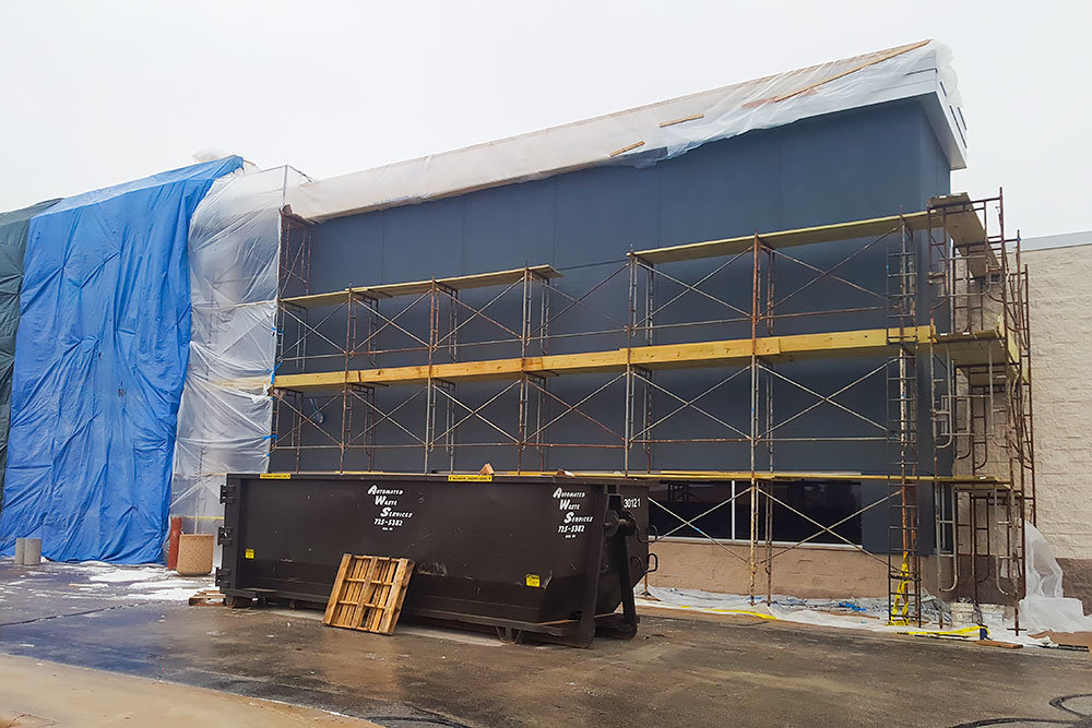 The exterior of the former Toys R Us building is covered by scaffolding and tarps on Thursday.