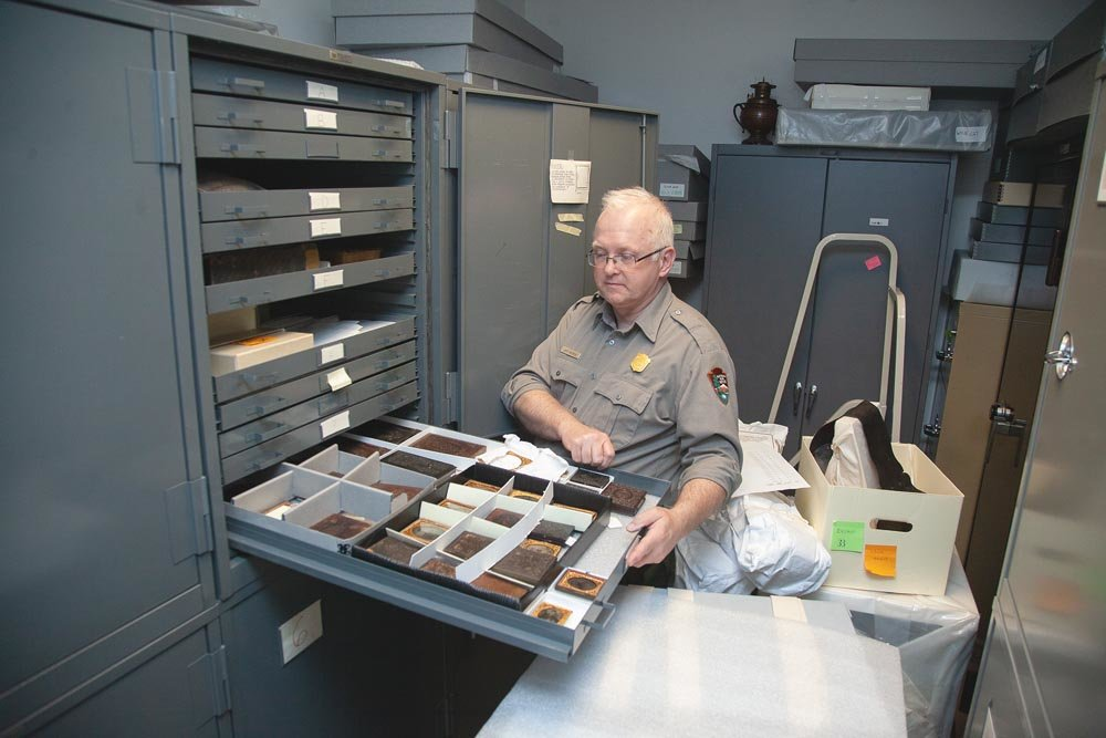 PRESERVING HISTORY: Museum curator Jeff Patrick goes through artifacts, such as artillery from the 1860s, stored in drawers and cabinets in the park's library due to lack of exhibit space.