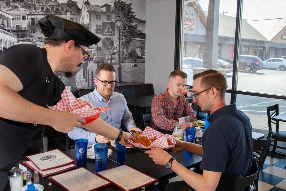 BURGERS AND BRANDING: Springfield Diner's Omer Onder serves lunch to Jeremy Wells, Dustin Myers and Tyler Barnes of Longitude.