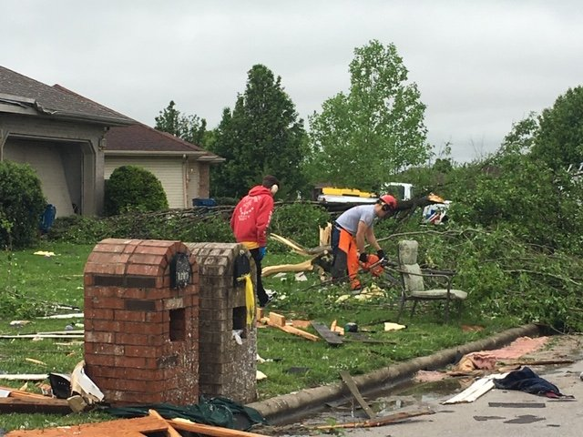 A crew with Convoy of Hope cleans up debris from Tuesday's storm in Ozark's Waterford subdivision.