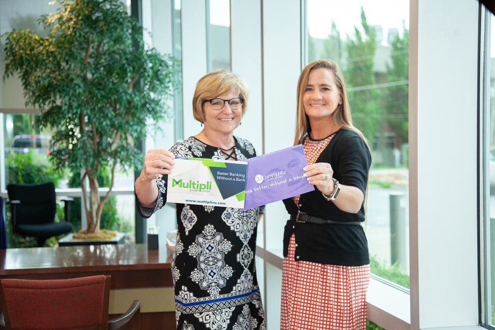 STATEMENT PIECE: Judy Hadsall, left, holds a flyer for the rebranded Multipli Credit Union, and Alisa Lawler contrasts the change with a CU Community Credit Union promotional piece. Credit unions are revamping their messaging.