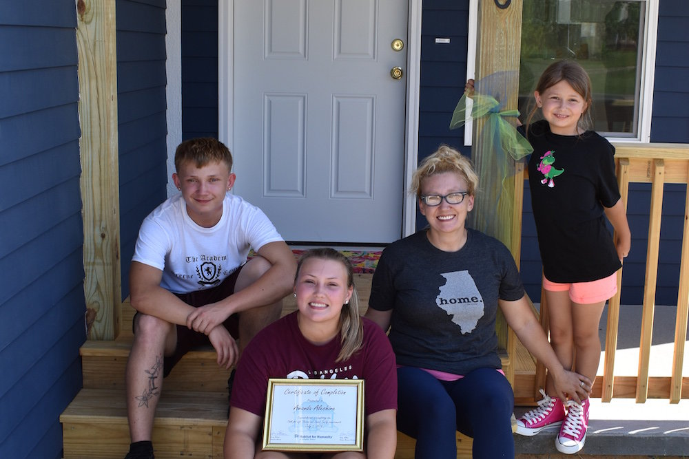 The new homeowner and her children pose outside the Habitat for Humanity home.