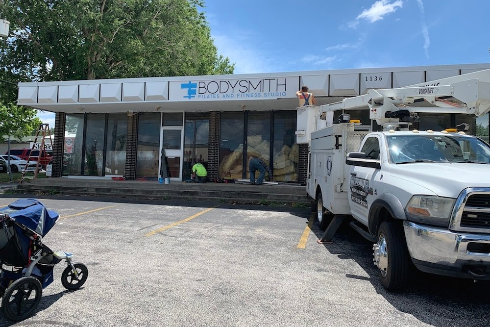 Crews install signage at The Bodysmith's new home.