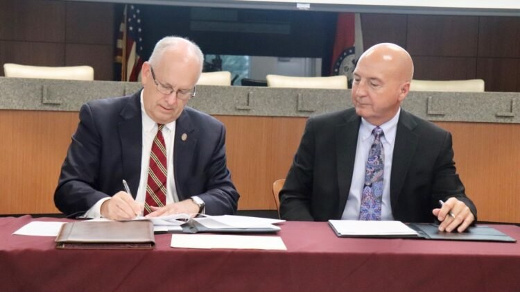Missouri State University President Clif Smart signs a dual-credit agreement with Blue Springs Public Schools Superintendent Paul Kinder.
