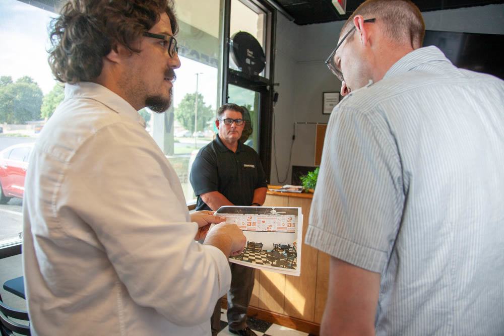 Longitude's Dustin Myers, right, shows a subway tile design to Springfield Diner owner Omer Onder, which he suggests for one of the walls. Darren Pearce, center, of Pinnacle Sign Group is on hand to talk exterior signage.