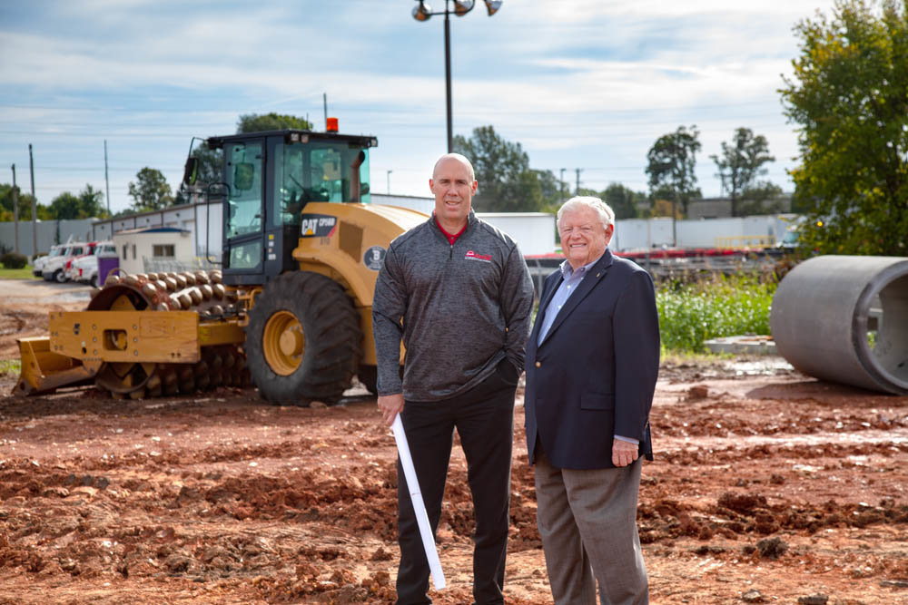 "POP EXPANSION: Ozarks Coca-Cola/Dr Pepper Bottling, led by CEO Edwin ""Cookie"" Rice, at right, and President and Chief Operating Officer Bruce Long, is in the midst of dirt work on a $15 million, 400,000-square-foot warehouse expansion."