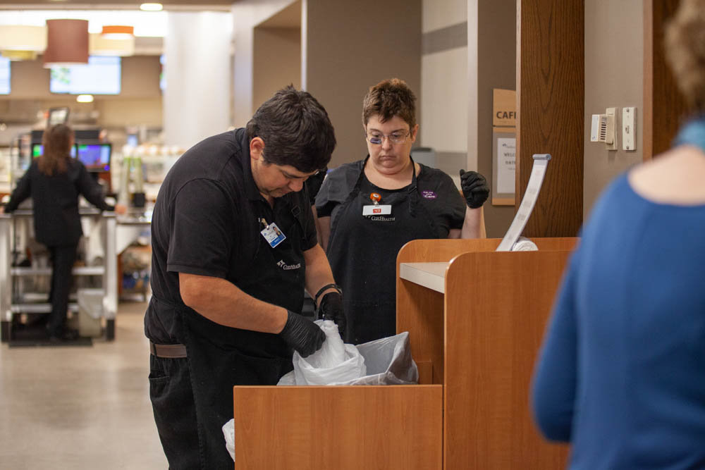 Developmental Center of the Ozarks employees Donnie Curran and Olive Henopp team up to change out trash receptacles in the Cox South Hospital cafeteria.