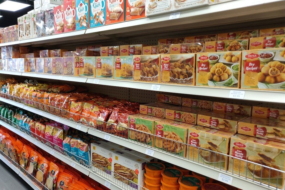 Food items including khari biscuits and dry kachori line the shelves at the new grocery.