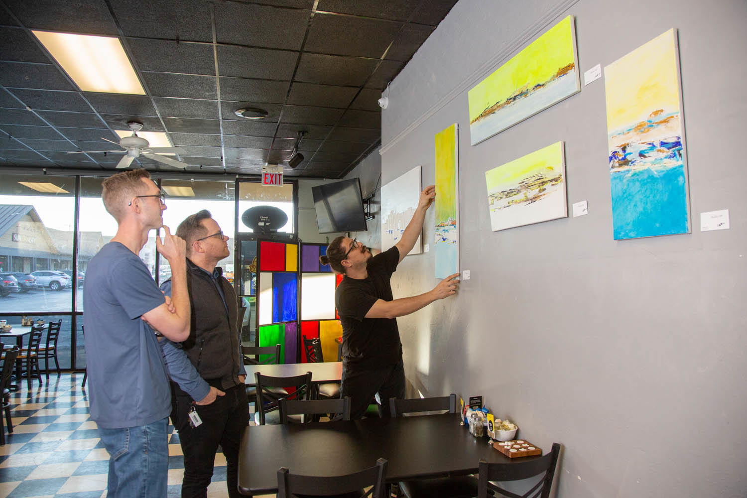 ARTISTIC IMPRESSION: Springfield Diner owner Omer Onder talks improvements at the restaurant with Longitude's Dustin Myers and Jeremy Wells as he adjusts new artwork on display.